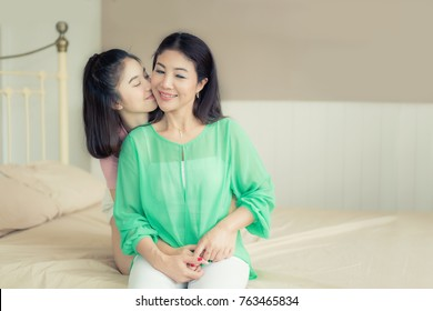 Asian love of mother and daughter. Happy woman in bedroom with copy space. Aged woman and her adult daughter kissing at bedroom in house. Mothers day.