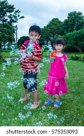 Asian lovely brother and sister smiling and playing together with soap bubbles gun at yard. Outdoor at the daytime with bright sunlight on summer day. Happy family on summer vacation concept.