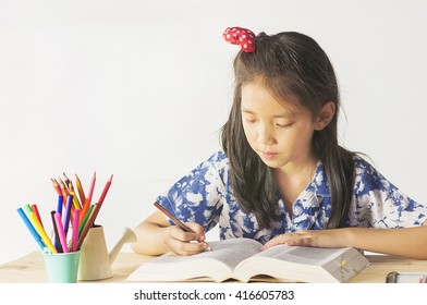 Asian lovely child is reading a book