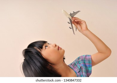 Asian lovely cute girl plays model airplane on pink background. Childhood creative imagination concept.