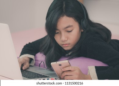 Asian lovely girl listens to music while on a bed and holds a smartphone in her hand with a sad face