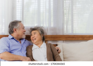 Asian lovely happy senior couple grandfather and grandmother hugging or cuddling on sofa in living room at home. Joyful elderly smiling retired lover embracing or holding in romantic moment of love