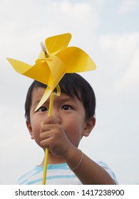 Asian lovely kid holding playing a yellow windmill toy with blue sky background. Cute young boy learning how turbine blow. Freedom and happy time. Preschool learning concept.