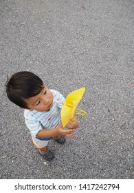 Asian lovely kid holding playing a yellow windmill toy with stone background. Cute young boy learning how turbine blow. Freedom and happy time. Preschool learning concept.