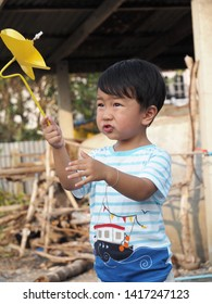 Asian lovely kid holding playing a yellow windmill toy with countryside background. Cute young boy learning how turbine blow. Freedom and happy time. Preschool learning concept.