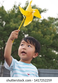 Asian lovely kid holding and playing a yellow windmill toy with happy face with natural background. Cute young boy learning how turbine blow. Freedom and happy time. Preschool learning concept.
