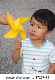 Asian lovely kid holding and playing a yellow windmill toy with dad with small stones background. Cute young boy learning how turbine blow. Freedom and happy time. Preschool learning concept.