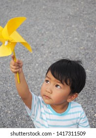 Asian lovely kid holding and playing a yellow windmill toy with happy face with small stones background. Cute young boy learning how turbine blow. Freedom and happy time. Preschool learning concept.