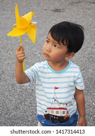 Asian lovely kid holding and playing a yellow windmill toy with serious face. Cute young boy thinking and learning how turbine blow. Freedom and happy time. Preschool learning concept.