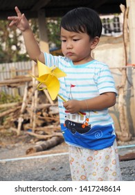 Asian lovely kid turning yellow windmill toy by hand with countryside background. Cute young boy playing and learning how turbine blow. Freedom and happy time. Preschool learning concept.