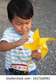 Asian lovely kid turning yellow windmill toy by hand with small stones background. Cute young boy playing and learning how turbine blow. Freedom and happy time. Preschool learning concept.