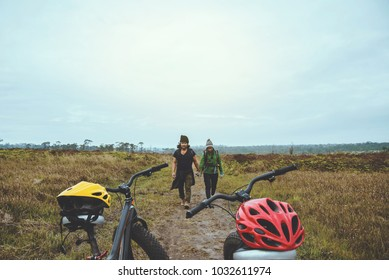 Asian lover women and men Travel photograph nature. Travel relax ride a bike Wilderness in the wild.Stand on the line. In the meadow in the woods. Thailand