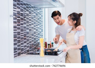 Asian lovers or couples cooking dinner in kitchen room. Man point to delicious food that woman making. Holiday and Honeymoon concept. Happy sweet home theme