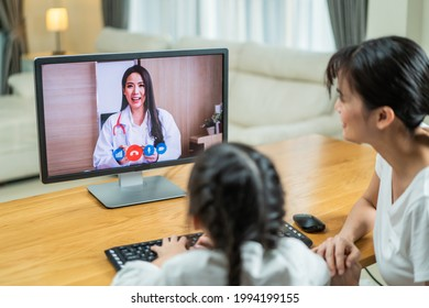 Asian loving Mother with little girl daughter use laptop for virtual video call with doctor in living room. Attractive pediatrician give online consult and treatment to small kid and family for health