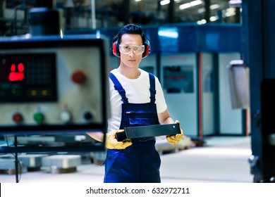 Asian machine operator in production plant checking data