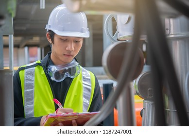 Asian Maintenance engineer at the waste water management system of a huge factory,maintenance checking technical data of heating system equipment,Thailand people