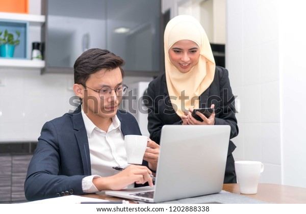 Asian malay executive working at home with laptop discussing