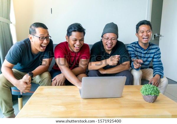 Asian Malay friends at apartment watching movie at laptop together having fun