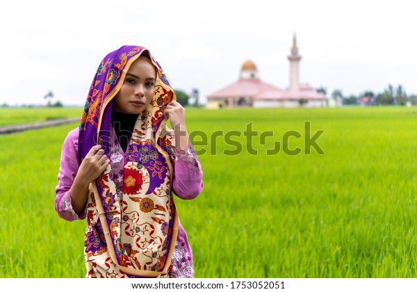 Asian malay lady wearing traditional cloth outdoor with mosque background
