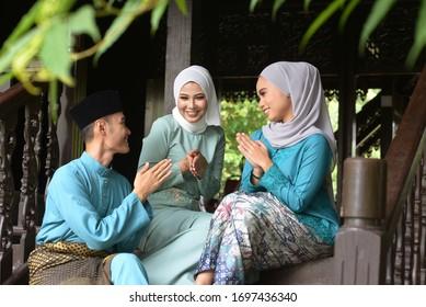 Asian Malay Muslim greetings during Hari Raya Aidilfitri. Malaysian people living lifestyle.