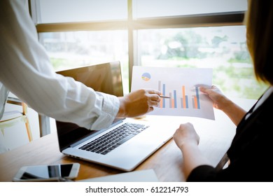 Asian Male accountant or banker making calculations. Savings, finance and economy concept.Coworking team.Closeup photo Young business managers working with new startup project in office.