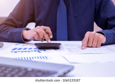 Asian male accountants or bankers perform calculations. Financial savings and economic ideas for 2018 through laptops in the office.