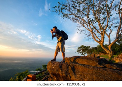 Asian male backpack in nature during sunset   Relax time on holiday concept travel at Pha mor i dang,Sisaket province,Thailand,ASIA.