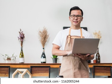 Asian male Barista cafe owner using laptop in cafe business inside coffee shop,looking and smile at camera.food and drink business start up.