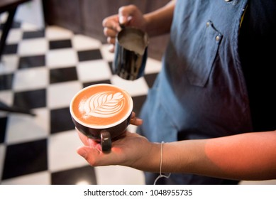 asian male barista create latte art in coffee shop.food and drink concept