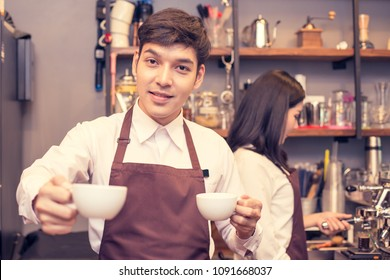 Asian male barista holding coffee cup in coffee shop counter.  Barista male working at cafe. Man working with small business owner or sme concept. Vintage tone.
