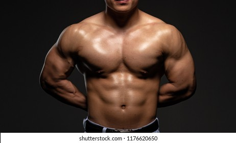 Asian male bodybuilder shooting in the studio, black background.