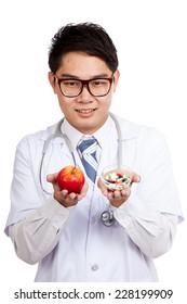 Asian male doctor with apple and medicine  isolated on white background