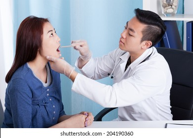 Asian male doctor examining his female patient