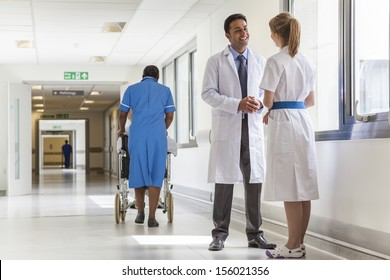 Asian male doctor & female nurse in hospital corridor with African American black nurse & senior female patient in wheelchair