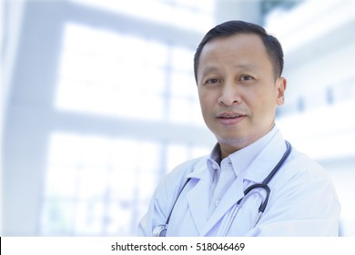 Asian male doctor with a happy smile on blurry white background