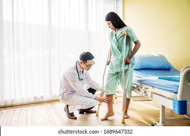 Asiatischer Arzt oder Physiotherapeut untersucht das Knie und hilft dem Patienten, mit Krücken zu gehen, weil verletzte Beine von jungen Patientinnen nach dem Unfall und erklärt ihr die Diagnose des Problems.
