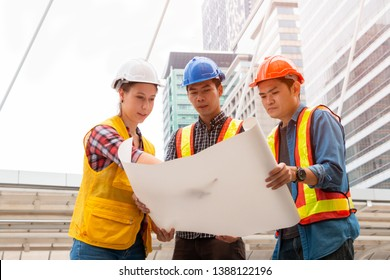 Asian male engineer, caucasian female engineer and technician operator with safety helmet and blueprint working at the construction site. Professional team in big city. Teamwork & engineering concept.