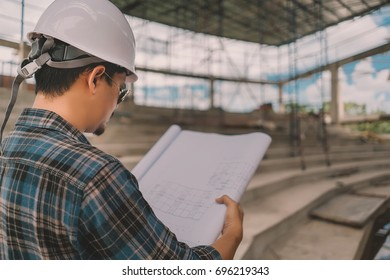 Asian male engineer looking at his design in the building and working outside the office ,Engineer concept,Off-site engineering concept .