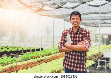 asian male farmer using laptop To collect data to study and develop his farm to improved productivity in the future.Good farming Theory of Asia.