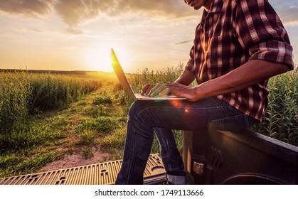 asiatischer männlicher Bauer, der im Bauernhof arbeitet, um Daten zu sammeln, um seinen Bauernhof zu studieren und zu entwickeln, um die Produktivität in der Zukunft zu verbessern.Gute landwirtschaftliche Theorie Asiens.Intelligentes Bauernkonzept.