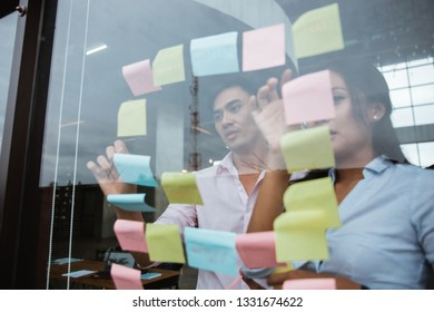 asian male and female business partner brainstorming by sticking idea into the glass window