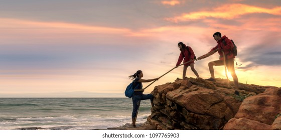 Asian male and female hikers climbing up  mountain cliff . helps and team work concept .