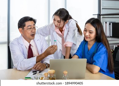 Asian male and female medical doctor team sitting at desk and meeting discussion about vaccine with laptop computer