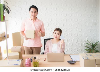 An Asian male and female Thai staffer dressed in a pink dress was smiling brightly in his hand, holding a parcel box. The face showed confidence in the quality of goods and friendly service.