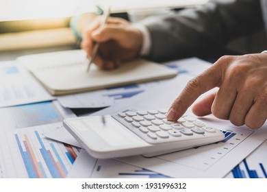 Asian male finance staff is calculating the investment results to deliver a report to his supervisor at the meeting. On the table in the office, the concept of calculating investment results