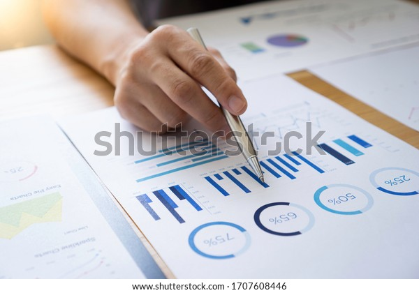 Asian male finance staff Is explaining the performance from the company's rapidly growing bar graph this year. To his boss On the desk at the office, Finance concept