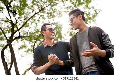 Asian male friends talking outdoors