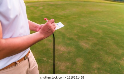 Asian male golfer using pen writing his golf score on scorecard while standing on green fairway.