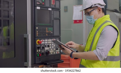 Asian male industrial engineers in new project while using tablet computer checking machine. They're making calculated engineering decisions. They work at the heavy industry manufacturing factory.