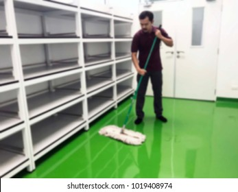 Asian male janitor mopping floor in classroom of school blur image use for background. Commercial cleaning and janitorial services concept.